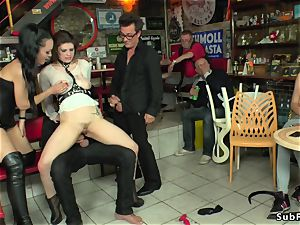 domme in leather dominates victim in public