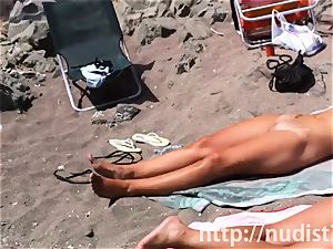 Spy web cam shot of a super-hot nudist babe tanning on the beach